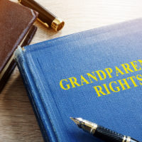 Book that reads Grandparents Rights addressing elder law with glasses on table