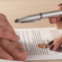 woman giving a pen to her spouse