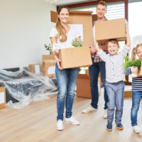 As a result of relocation, a family packs up boxes with children