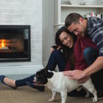 Couple relaxing with their pet dog in living room